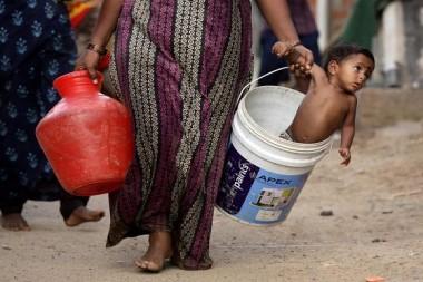 Una mujer lleva a su hijo en un balde después de recoger agua de un camión cisterna municipal en las afueras de Chennai, India, 4 de julio de 2019